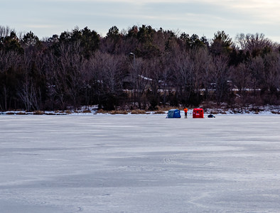 Ice fishing on frozen Ed Zorinsky lake Omaha Nebraska US in winter. Two ice shanties, a red and a blue one on frozen lake surface with a fisherman in between them.