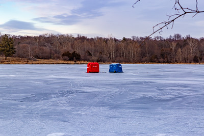 Ice fishing on frozen Ed Zorinsky lake Omaha Nebraska US in winter. Two ice shanties, a red and a blue one on frozen lake surface.