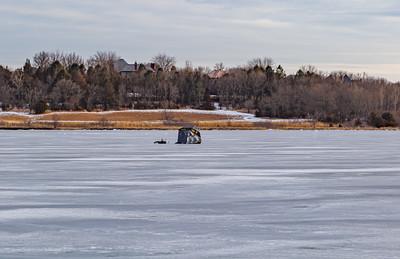 Ice fishing on frozen Ed Zorinsky lake Omaha Nebraska US in winter. One black ice shanty on frozen lake surface.