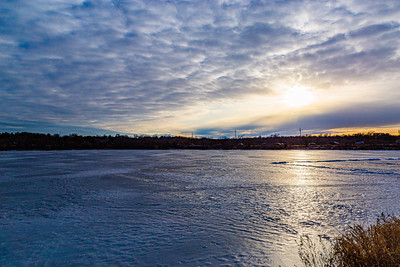 Frozen Ed Zorinsky lake in winter with sunset rays reflection on frozen lake surface.