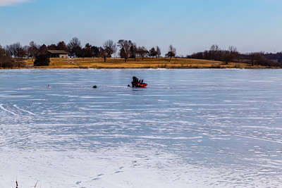 Ice fishing on frozen Ed Zorinsky lake Omaha Nebraska US in winter. A fisherman is sitting on a chair on frozen lake surface. Tending multiple holes and tackles.