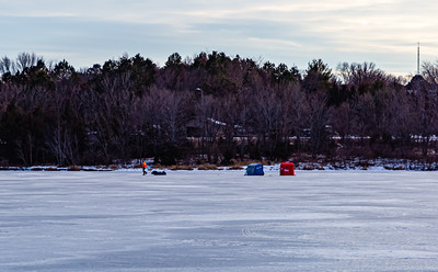 Ice fishing on frozen Ed Zorinsky lake Omaha Nebraska US in winter. Two ice shanties, a red and a blue one on frozen lake surface.  A fisherman is sledding his stuff away.