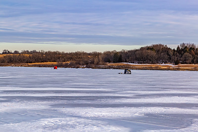 Ice fishing on frozen Ed Zorinsky lake Omaha Nebraska US. Two ice shanties, a red and a black one on frozen lake surface.