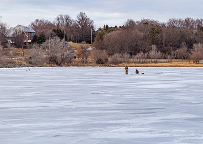 Ice fishing on frozen Ed Zorinsky lake Omaha Nebraska US in winter. Two fishermen dressed for the cold weather  on frozen lake surface.