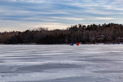 Ice fishing on frozen Ed Zorinsky lake Omaha Nebraska US. Two ice shanties, a red and a blue one on frozen lake surface.