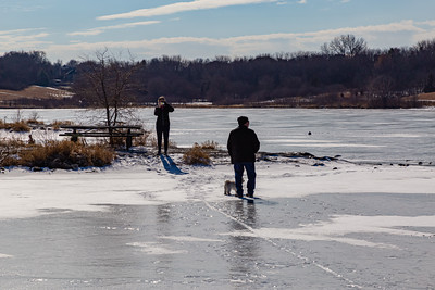 A couple taking photos with their dog on frozen lake surface at Ed Zorinsky lake in winter.