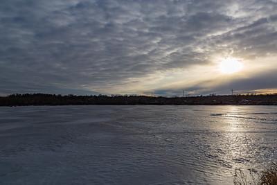 Frozen lake surface in winter with sunset reflections on the frozen surface. Ed Zorinsky lake park Omaha Nebraska.