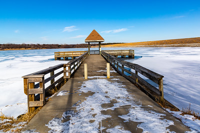 Frozen pier on frozen Ed Zorinsky lake Omaha Nebraska in winter.