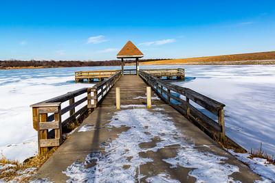 Frozen pier on frozen Ed Zorinsky lake Omaha Nebraska in winter.
