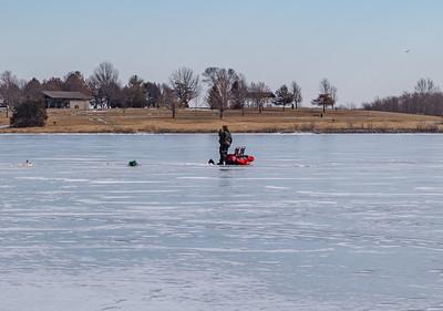 Ice fishing on frozen Ed Zorinsky lake Omaha Nebraska US in winter. A fisherman tending holes and tackles on frozen lake surface.