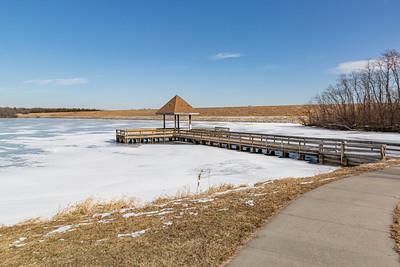 Frozen lake surface with frozen pier in winter. Ed Zorinsky lake Omaha Nebraska.
