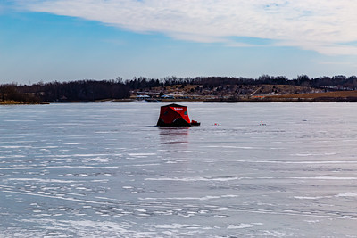 Ice fishing on frozen Ed Zorinsky lake Omaha Nebraska US in winter. A red ice shanty on frozen lake surface.