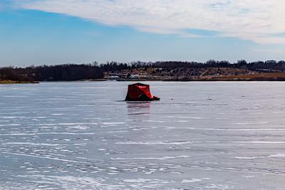 Ice fishing on frozen Ed Zorinsky lake Omaha Nebraska US in winter. A red ice shanty on frozen lake surface.