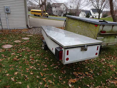 Custom Trailer for the DN.    Automatic Slide-in Pins hold the front down and the padlock hasp holds the back down.  Note: huge tail lights; plus, reflectors if parked on the street at night.