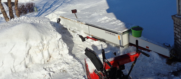 Digging out.  Green bucket of sand balances the snow load.