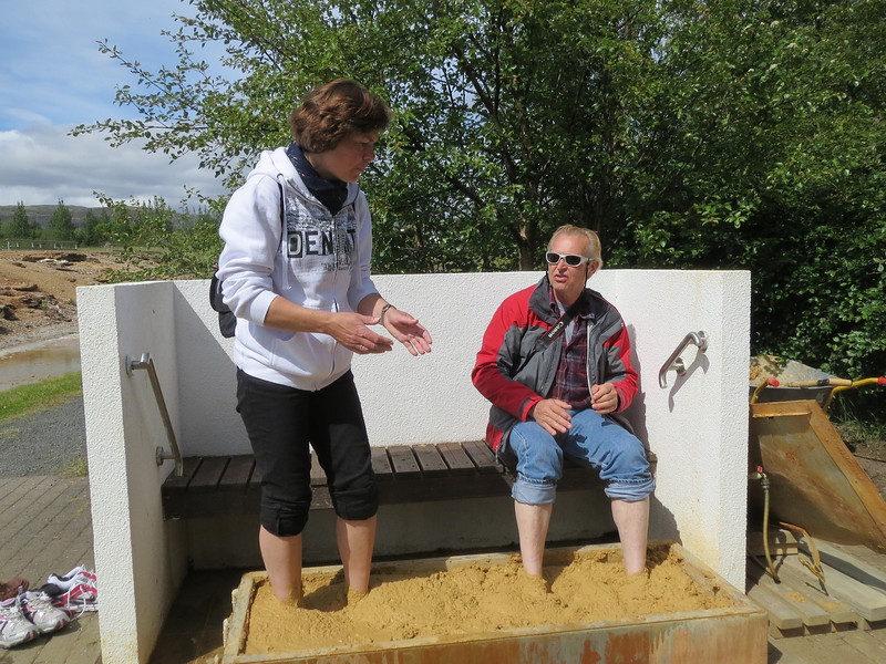 Steve talking with a Norwegian lady while getting the hot mud treatment to the feet in the town of Hveragerdi.