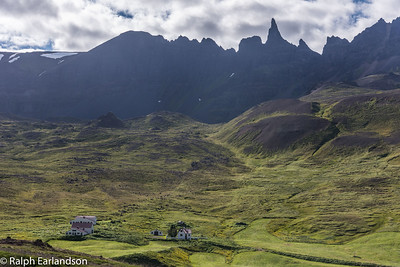 Jagged mountains of northern Iceland overshadow the houses.