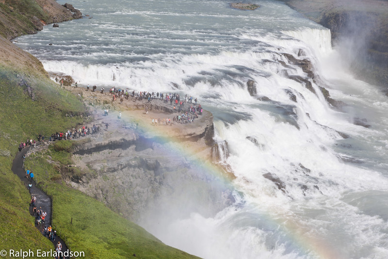Gullfoss: Iceland's Golden Falls with a rainbow and many spectators.