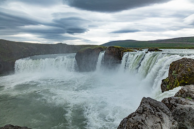 """Goðafoss is a waterfall the Bárðardalur district of Northeastern Region of Iceland.  The water of the river Skjálfandafljót falls from a height of 12 meters over a width of 30 meters.The river has its origin deep in the Icelandic highland.  In 999 AD,  Christianity became the official religion of Iceland by the Alþingi, the newly formed Icelandic parliament.   According to a modern myth, it is said that upon returning from the, the Icelandic leader Þorgeir threw his statues of the Norse gods into the waterfall.  In the Icelandic language, Goðafoss means """"waterfall of the gods"""" or """"waterfall of the goði""""."""