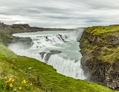 """Gullfoss is a waterfall located in a canyon of Hvítá river in southwest Iceland near the town of Geysir.  Gullfoss, translated as Golden Falls, is one of the most popular tourist attractions in Iceland. The wide Hvítá river flows into a wide curved three-step """"staircase"""" and then abruptly plunges in two stages  of 36 feet and 69 feet respectively.  The average amount of water flowing down the waterfall is 4,900 cu ft per second in the summer and 2,800 cu ft per second in the winter."""