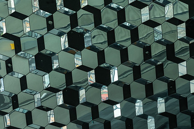 The ceiling of Harpa, a concert hall in Reykjavík, Iceland.   The building features a distinctive colored glass facade inspired by Iceland's basalt landscape and its distinctive hexagonal shapes.  The structure consists of a steel framework clad with geometric shaped glass panels of different colors.