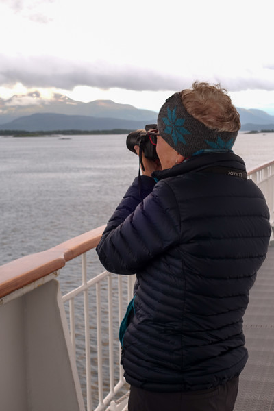 Bev doing some photography on deck as we're heading toward Geiranger Fjord
