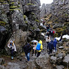 tourists walk up the gap between two tectonic plates at thingellvir iceland