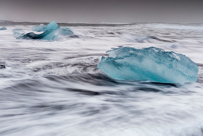 Blue ice against a white and black background of stark colors and giant waves