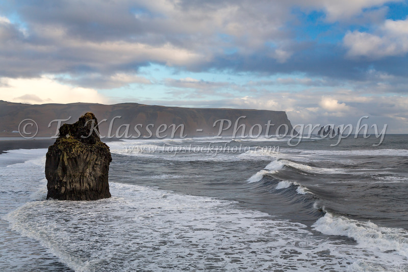 Rock formations with waves and surf on the Dyrholaey coast in southern Iceland.