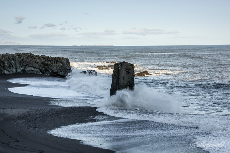Laekjavik coast line with basaltic pillar and offshore Papaey bird island (on horizon mid image) , East Fjords, Iceland
