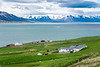 Farm buildings on the plains beside the  Eyjafjörður fjord, near Grenvik, Iceland, Europe.