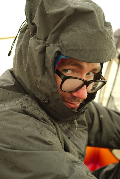 Yann trying to warm up in the tent after cooking breakfast in the freezing rain