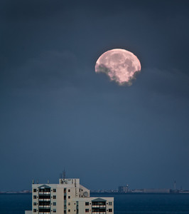 Moon rises over Akranes, with a Reykjavik building in the foreground.