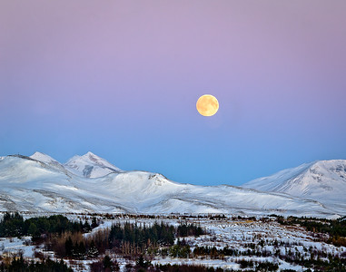 A yellowish moon rising over the mountains north of Reykjavik, the capital of Iceland.