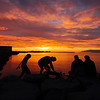Locals gather along the water to witness a particularly incredible setting of the midnight sun