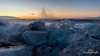Sunrise and beaking waves hitting the jumbled ice  at Diamond Beach, Jökulsárlón, Iceland