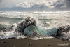Storm wave smashing into blue ice on the shore, Diamond Beach, Iceland