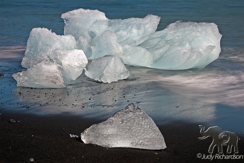 Colorful glacial ice from  Breiðamerkurjökull Glacier and Jökulsárlón Lagoon  on black sand beach