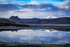 The coastal mountains of southern Iceland reflected in a small lake.