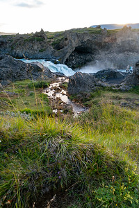 Two People Looking Over the River Rapids Near Godafoss Waterfall in Iceland