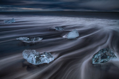 Icebergs on volcanic beach at dusk, Iceland
