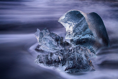 Iceberg on volcanic beach at dusk, Iceland
