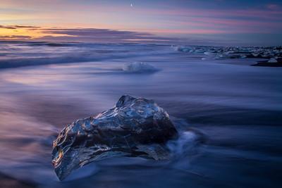 Sunset, moonrise, and icebergs on a black sand beach, Iceland