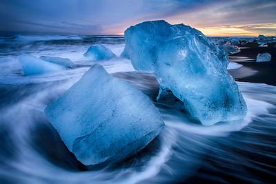 Icebergs on volcanic beach at sunset, Iceland