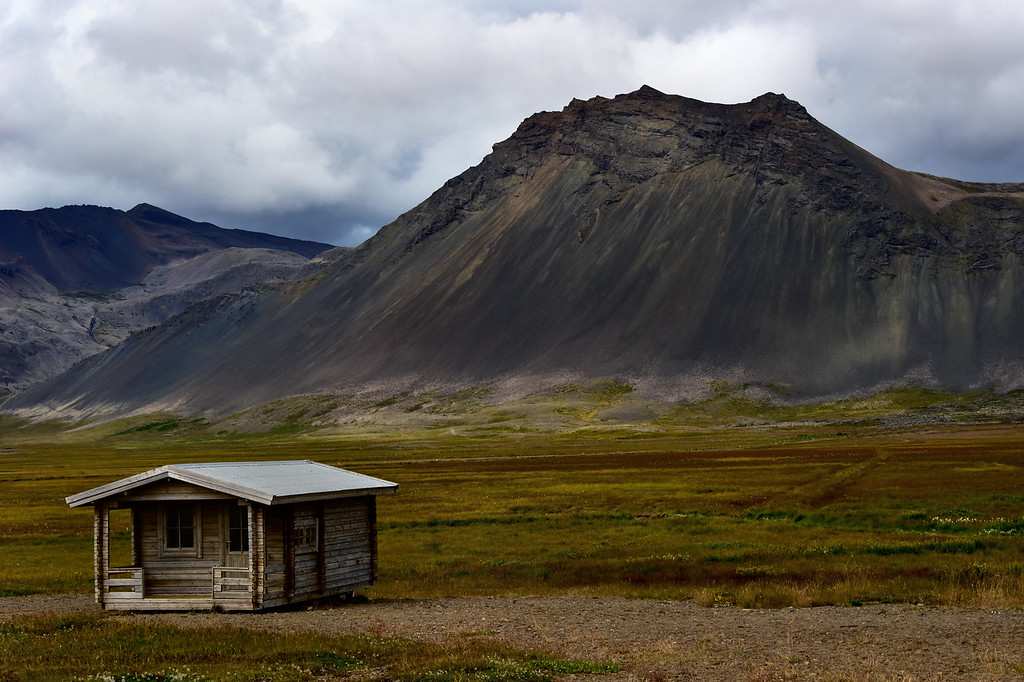 Roadside wooden cabin with mountain in background, Iceland