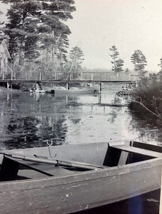 Original wooden bridge to island with one of the  wooden boats in foreground, circa mid to late 1940's