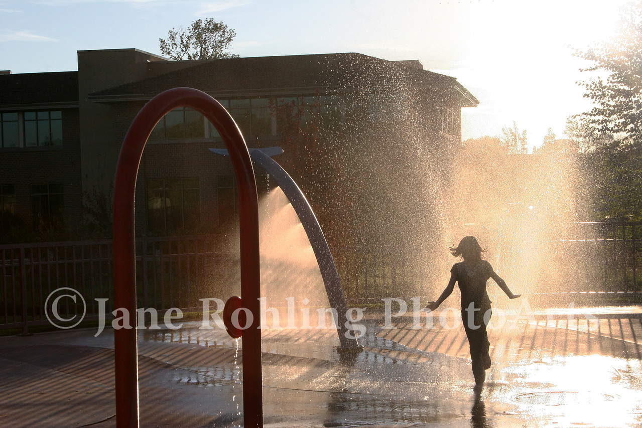 Girl running through water spray at Merrill Park in Eagle, Idaho.