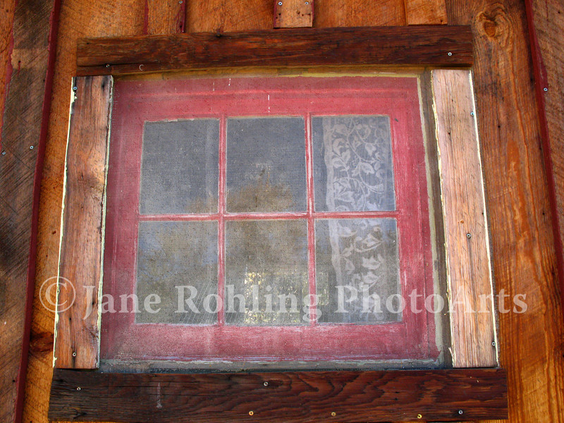 Lace curtains in the window of a rustic shed near Fairfield, Idaho.