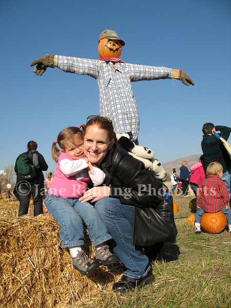 A  happy mother and daughter pose with a scarecrow in the pumpkin patch, Thunder Mountain Railroad, Horseshoe Bend, Idaho.