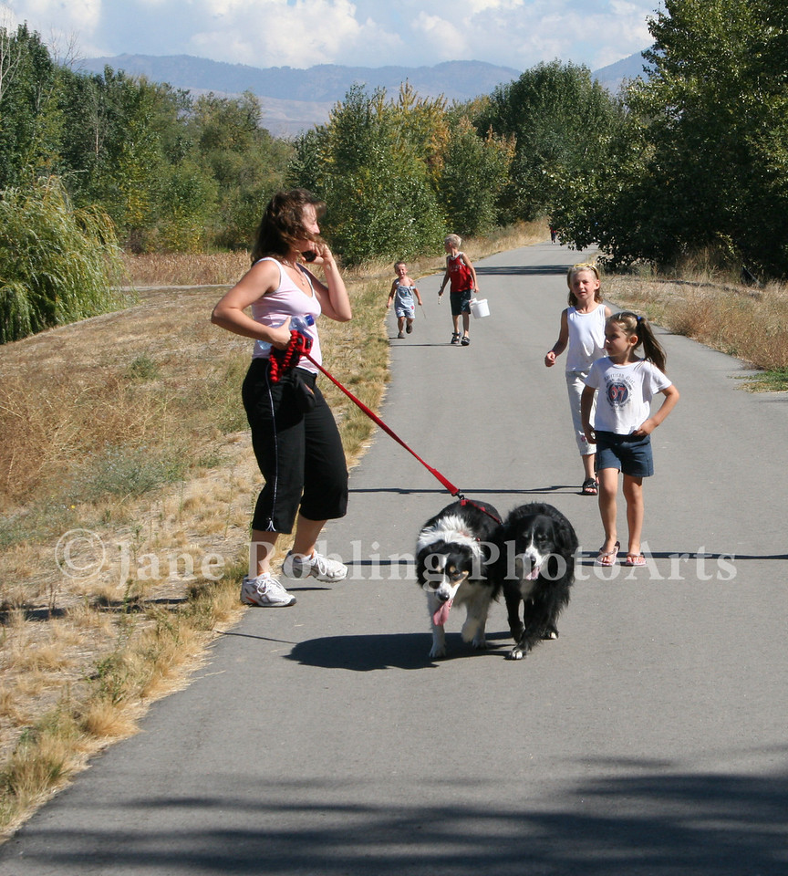 Family with dogs walking on the greenbelt along the Boise River in Eagle, Idaho.